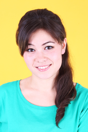 pretty young asian girl over yellow background Stok Fotoğraf