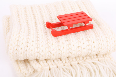 red wooden sledge christmas souvenir on the white scarf  Stock Photo