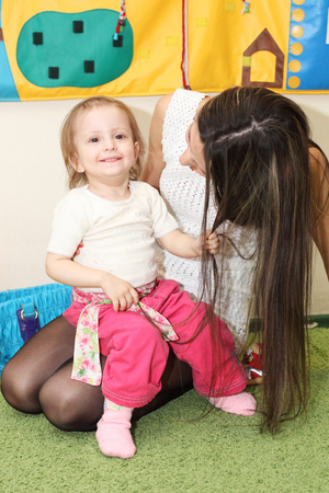 cute little girl holding her mothers long hair