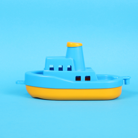 little plastic toy ship on the blue background Stock Photo