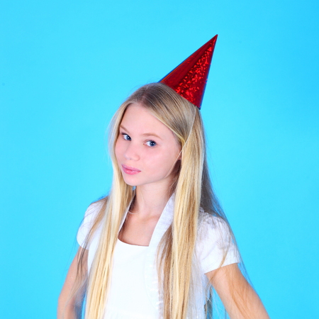 pretty teenage girl in the white dress and birthday cap 写真素材