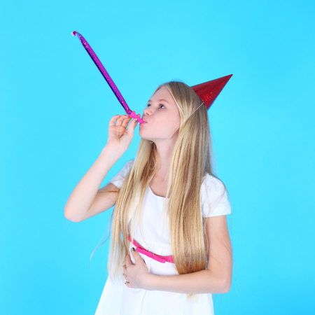 pretty teenage girl in the white dress and birthday cap Stock Photo