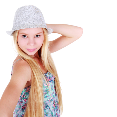 beautiful teenage girl posing in the summer dress with the hat