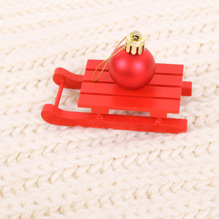 red wooden sledge christmas souvenir on the white textile