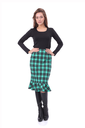 pretty young girl wearing black top and green checked skirt with high boots  isolated on white Stockfoto
