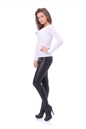 pretty young girl wearing white top and black leather trouser  isolated on white