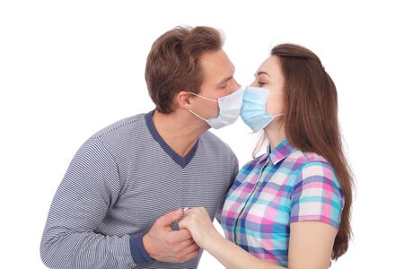 young couple kissing in medical masks