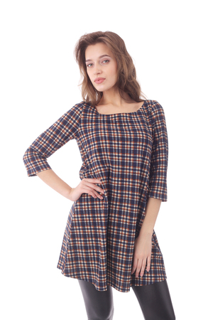 pretty young woman wearing check tunic and black pants Stock Photo