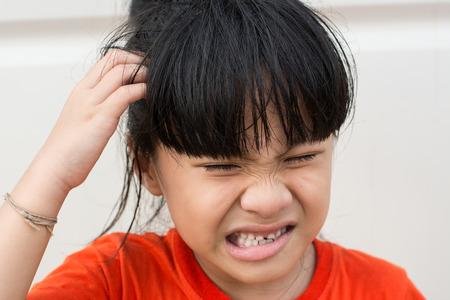 puzzelen: Mad Child, omdat luizen op het hoofd. Stockfoto