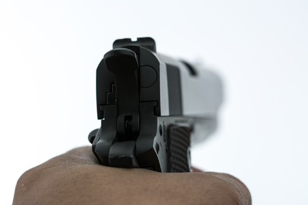 Hand shooting with a gun on white