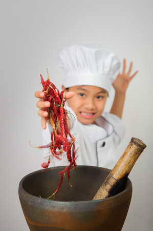 Young cooks or chef child are cooking and have chili in hand,papaya salad,Somtum very spicy,very hot