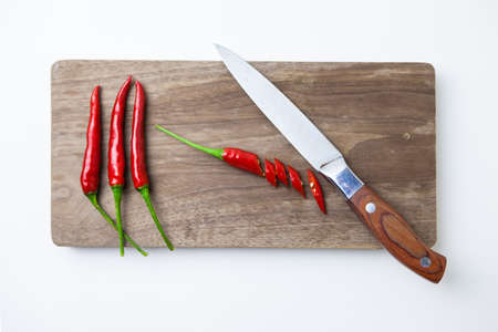 Chili peppers on a cutting board with knife