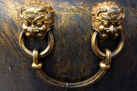 Chinese dragon's face appears on handles of large bronze vat. Reklamní fotografie