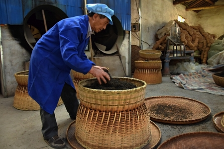 ANHUI PROVINCE, CHINA - CIRCA OCTOBER 2017: Man inside the tea factory in the process of packaging famous black tea Liu An. Redakční