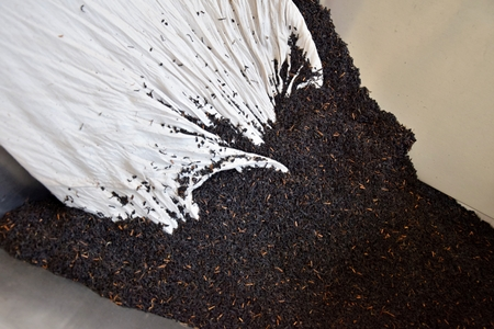 Close-up of the dry black tea leaves pouring out of the white sack.