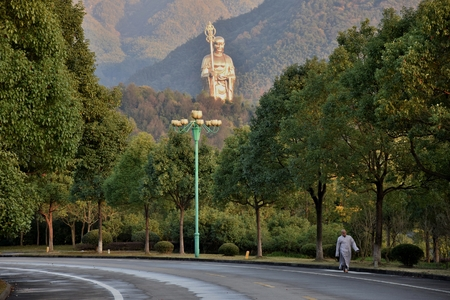 MOUNT JIUHUA, ANHUI PROVINCE, CHINA   CIRCA OCTOBER 2017: Two monks walking in front of statue of Dizang Pusa, Bodhisattva who is known in Mahayana Buddhism as the protector of creatures in the hell. Editorial