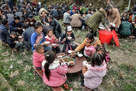 GUIZHOU PROVINCE, CHINA - CIRCA DECEMBER 2017: A group of people of different ethnic minority sit together on the occasion of a wedding feast.