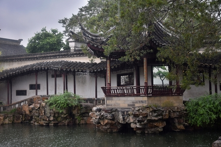 The gazebo in the chinese garden. Small pond, rocks around and the gazebo are traditional architectonical elements of chinese gardens.