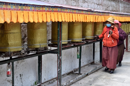 LHASA, TIBET AUTONOMOUS REGION, CHINA - CIRCA MAY 2018: Two women walking along tibetan prayer wheels.