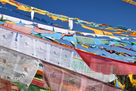 Tibetan prayer flags, colorful rectangular clothes, use to bless the surrounding countryside, blowing in the wind, blue sky in the background.
