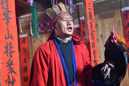 GUIZHOU PROVINCE, CHINA – CIRCA DECEMBER 2018: The ritual redeeming the vow in a village of Guizhou accompanied by theatrical performance did by the ritual masters. Translation of text: worship nature and ancestors.