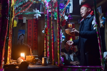 GUIZHOU PROVINCE, CHINA – CIRCA DECEMBER 2018: The ritual redeeming the vow in a village of Guizhou accompanied by theatrical performance did by the ritual masters. Translation of text: worship
