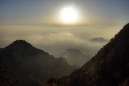Sunrise over the Emei mountain with top of the hills hidden in the clouds.
