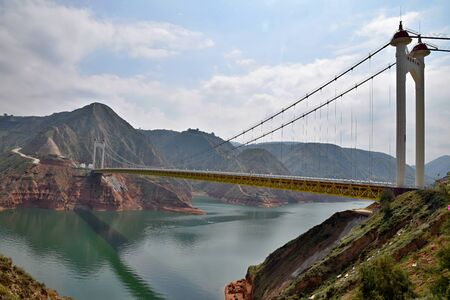The Liujiaxia Bridge over a Yellow River in Gansu province in China is the longest bridge of Gansu province. It was built in 2012 and it is 536 m long. Banco de Imagens