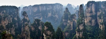 Zhangjiajie mountains in Hunan province in China. Thousand and thousand rock soar to skyward. The evergreen pine trees struggle on the top of the hills. Banco de Imagens