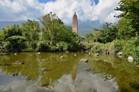 Reflection Pond mirroring the image of the Three Pagodas of the Chongsheng Temple near the old town of Dali in Yunnan province in China.