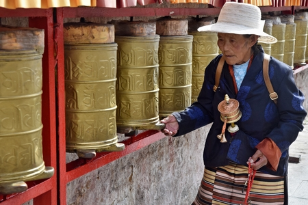 LHASA, TIBET AUTONOMOUS REGION, CHINA - CIRCA OCTOBER 2019: A man walking along the tibetan prayer wheels. Editorial