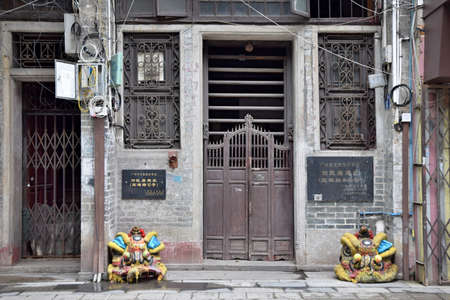 A historical building of Guangzhou with its traditional old-fashioned sliding wooden poles door and lion head in front of the house. Translation  of text: Historical building of Guangzhou.