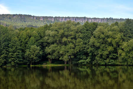 Forest landscape with natural lake in the foreground and famous Tisa Rocks in the background. Countryside of the Czech Republic in summer.