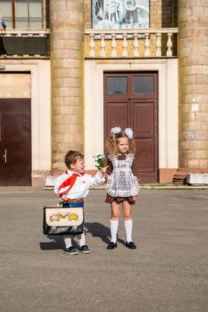 children in school uniforms with a briefcase walk near the school Stockfoto