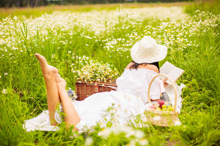 a girl in a white dress walks in a chamomile field with daisies