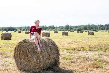 young woman sitting on hay bale Standard-Bild