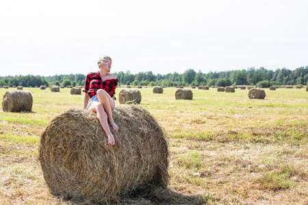 young woman sitting on hay bale Imagens