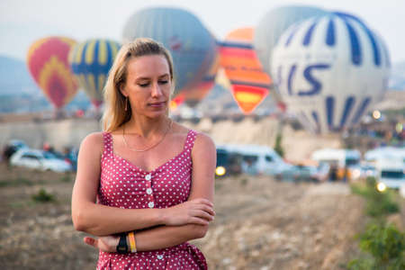 a girl is walking against the background of balloons in cappadocia