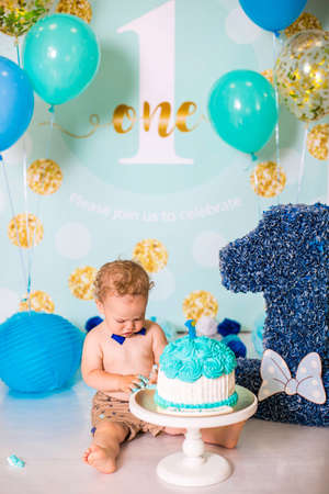 Baby boy playing with a cake during cake smash birthday party