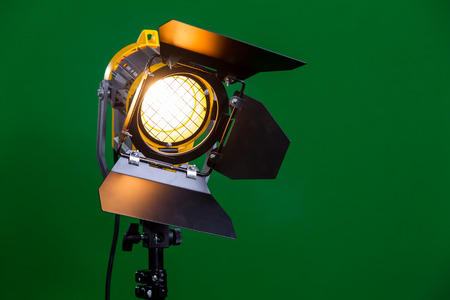 Halogen spotlight with a Fresnel lens on green background close-up. Stock Photo