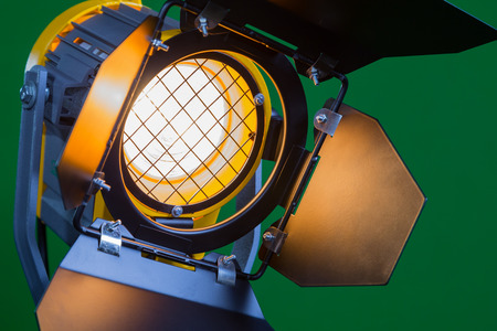 Halogen spotlight with a Fresnel lens on green background close-up. 스톡 콘텐츠