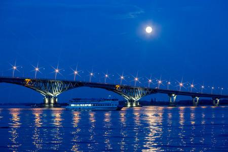 Evening or night landscape. The moon was full. Road bridge across the Volga river in Saratov, Russia.