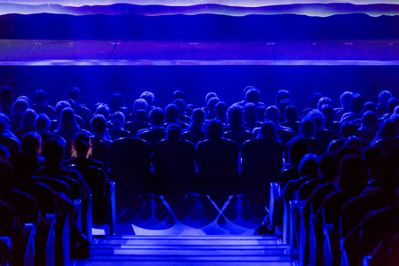 People in the auditorium looking at the stage. Shooting from the back Reklamní fotografie