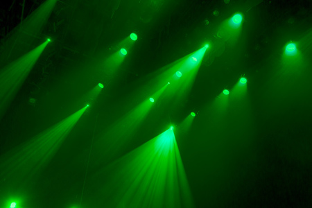 nightspot: The green light from the spotlights through the smoke in the theatre during the performance. Lighting equipment.