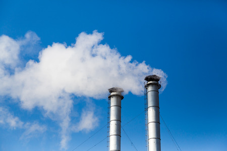 The smoke from the chimneys of a heating plant in the background of blue sky. Pollution of the environment. The exhaust emissions from the chimneys into the atmosphere