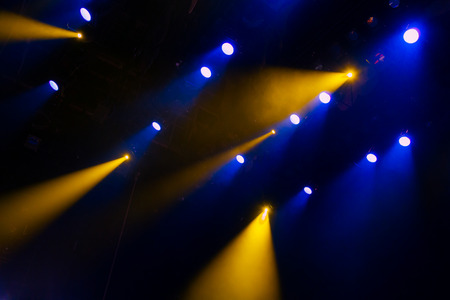 nightspot: The blue-yellow light from the spotlights through the smoke in the theatre during the performance. Lighting equipment.