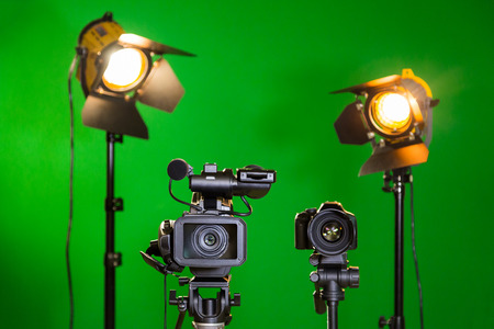 Two spotlights with Fresnel lenses, camcorder and SLR camera on a green background. Shooting in the interior with artificial light. The chroma key.
