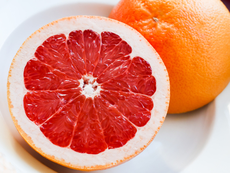 Half of a pink grapefruit on the plate. Stock Photo