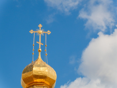 The Golden dome of an Orthodox temple on background of blue sky and clouds. Golden cross on the dome of the temple. Stock Photo