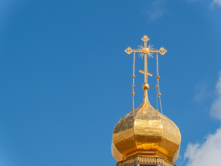De gouden koepel van een orthodoxe tempel op de achtergrond van de blauwe lucht en de wolken. Gouden kruis op de koepel van de tempel. Stockfoto